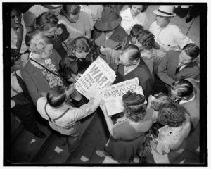 """A black and white photo shows a birds eye view of a crowd of people huddled around newspapers with headlines reading """"War: Bombs Rain on Warsaw"""" and """"Poland Invaded: Cities Bombed"""""""