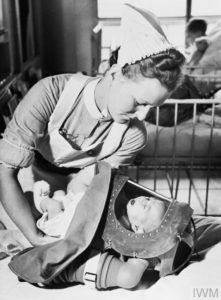 A nurse places a crying baby into its gas respirator during a drill at a London hospital.