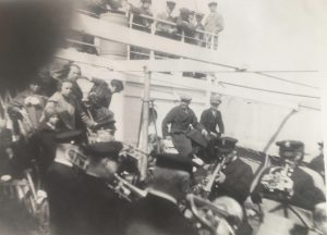 A black and white photo of a ship, crowded with people. There is a band playing brass music in the foreground while onlookers site in the background and stand along the rail on the upper deck.