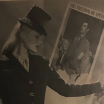 "This advertisement is in black and white, and depicts a woman in what is likely meant to be a street, though it more closely resembles a small, spare white-painted room. The woman has shoulder length blonde hair which is neatly combed back and is wearing some makeup, although her face is shadowed. She has a tall, slim build. She is wearing a dress suit, which consists of a loosely fitted blazer with full-length sleeves, and a skirt that goes to her mid-calf. There are four, large, decorative buttons closing the blazer. The blazer has a v-neckline, which reveals a white blouse beneath it. The woman holds a large clutch in her right hand. She rests her left hand on the ""Freedom of Worship"" poster on the wall next to her, which says ""BUY WAR BONDS"" in bold letters along the bottom. Another poster, ""Freedom of Speech,"" is visible behind her."