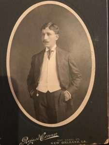 """A sepia toned studio portrait of a mustachioed man wearing a jacket, white vest, pleated pants, and tie. A pocket watch hangs on a chain from his vest pocket. He is posing with his hands in his pockets, looking past the camera and into the distance. Below the photo is the photography studio's name, """"Rojas Conner,"""" and the address of the studio, 1007 Canal St., New Orleans, LA."""